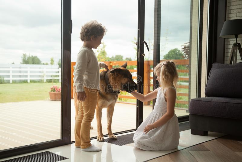 Jonge geitjes die met grote Duitse herdershond spelen die binnen huis komen stock foto's