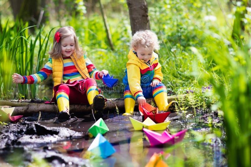 Jonge geitjes die met kleurrijke document boten in een park spelen royalty-vrije stock afbeeldingen