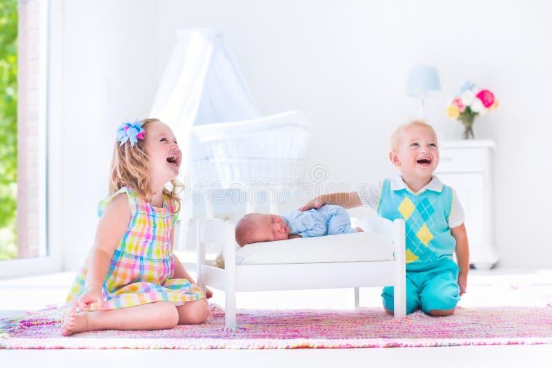 Jonge geitjes die met nieuw spelen - geboren babybroer royalty-vrije stock foto