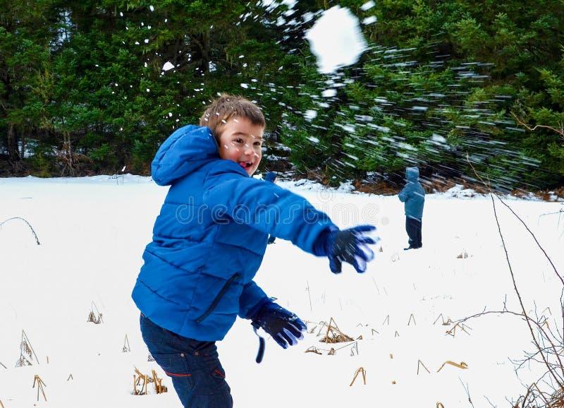 Jonge geitjes die met sneeuw spelen stock afbeeldingen