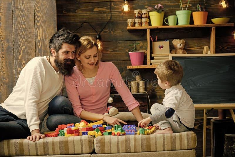 Jonge geitjes die met speelgoed spelen Vader, moeder en leuk zoonsspel met aannemersbakstenen Het geven oudersconcept Familie op  stock foto
