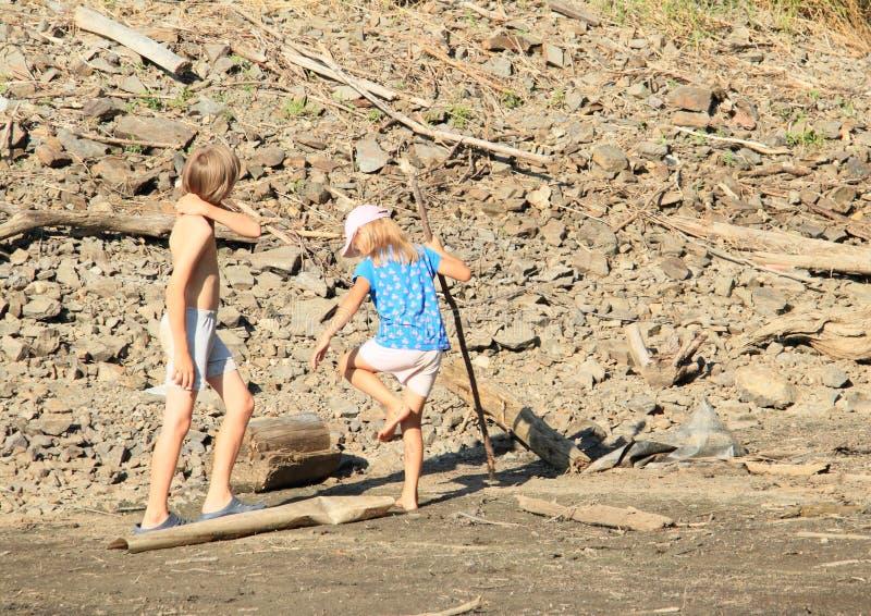 Jonge geitjes die in modder lopen stock afbeeldingen