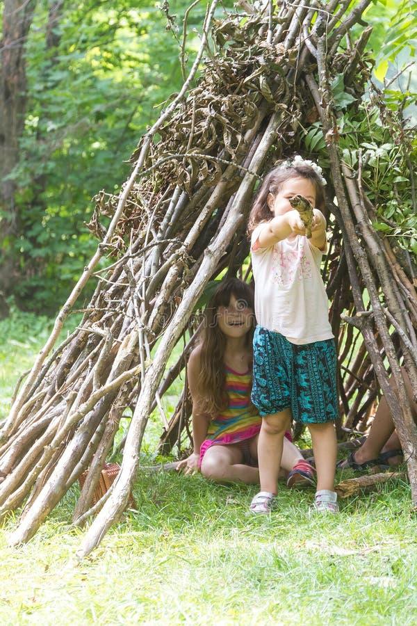 Jonge geitjes die naast het houten stokhuis kijken als Indische hut spelen, stock fotografie