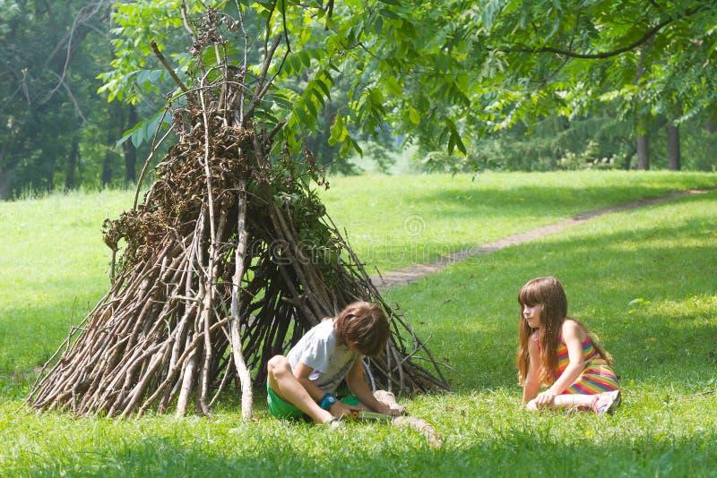 Jonge geitjes die naast het houten stokhuis kijken als Indische hut spelen, royalty-vrije stock afbeelding