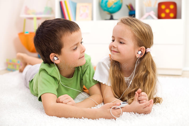 Jonge geitjes die oortelefoons delen die aan muziek luisteren stock fotografie