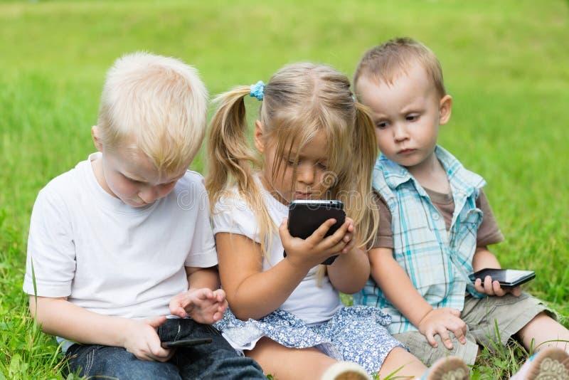Jonge geitjes die op smartphones spelen die op het gras zitten royalty-vrije stock foto's