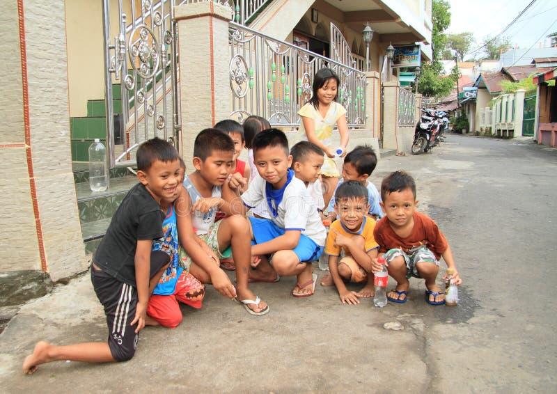 Jonge geitjes die op straat van Manado spelen stock fotografie