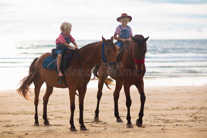 Jonge geitjes die paard berijden op strand De kinderen berijden paarden stock afbeeldingen