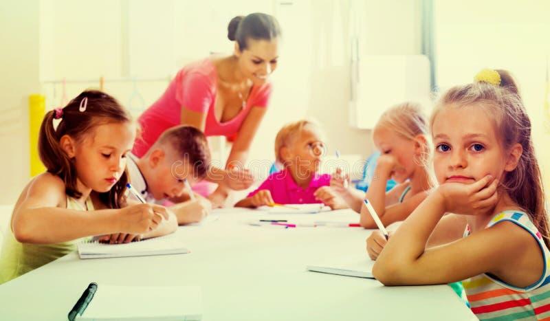 Jonge geitjes die samen met privé-leraar bij schoolklasse schrijven stock afbeelding