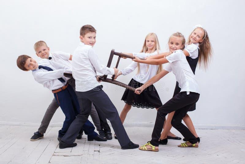 Jonge geitjes die sleepboot van stoel spelen - meisjes tegenover jongens stock foto's