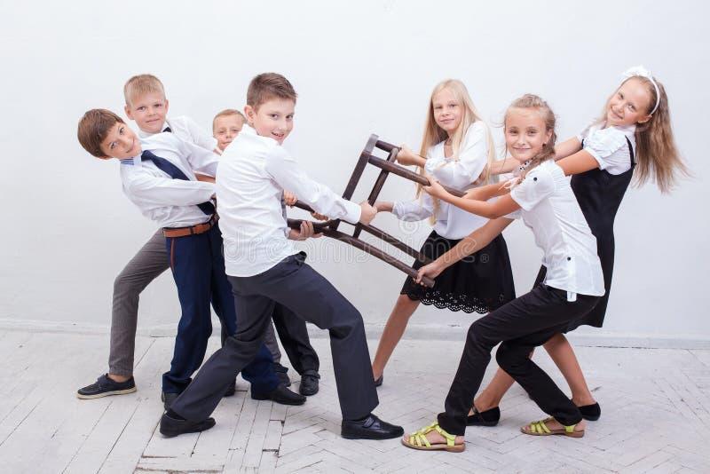 Jonge geitjes die sleepboot van stoel spelen - meisjes tegenover jongens stock fotografie