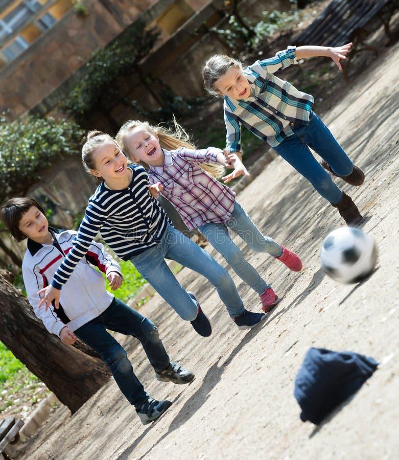 Jonge geitjes die straatvoetbal in openlucht spelen stock afbeelding