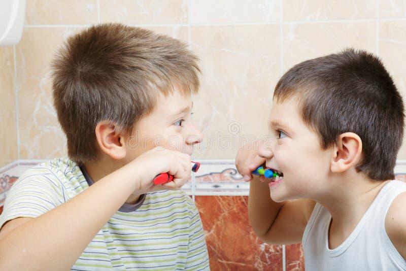 Jonge geitjes die tanden borstelen stock afbeeldingen