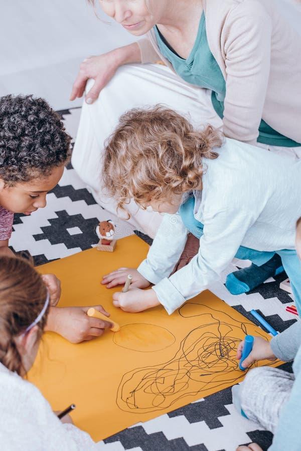 Jonge geitjes die tijdens creatieve activiteiten trekken royalty-vrije stock afbeelding