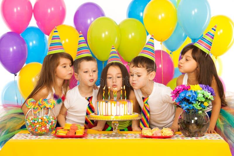 Jonge geitjes die verjaardagspartij en het blazen vieren stock fotografie