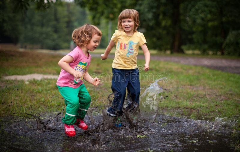 Jonge geitjes die in Watervulklei springen stock foto's