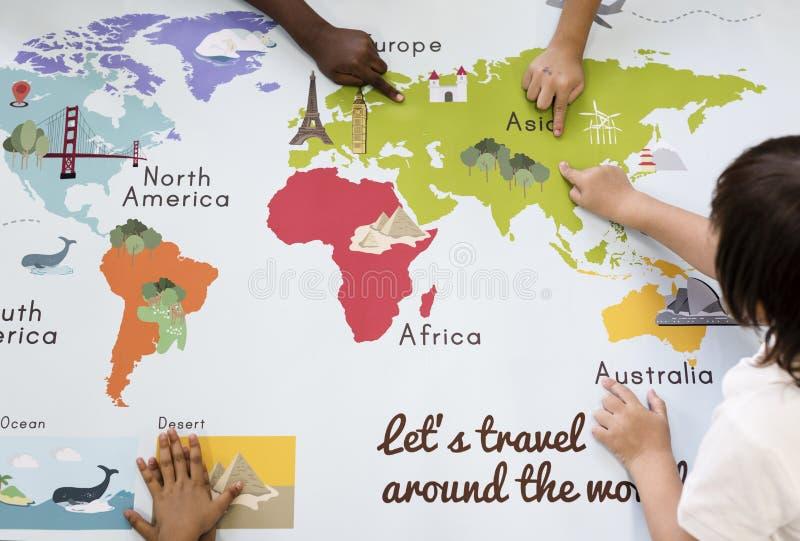 Jonge geitjes die Wereldkaart met Continentenlanden Oceaangeograph leren stock afbeelding