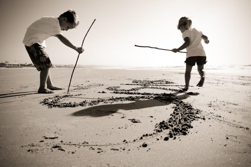 Jonge geitjes die in zand schrijven stock afbeeldingen