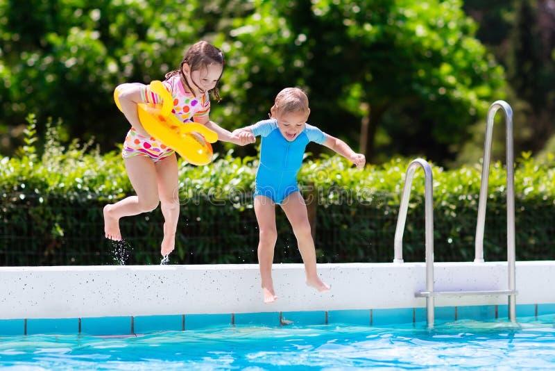 Jonge geitjes die in zwembad springen royalty-vrije stock afbeelding