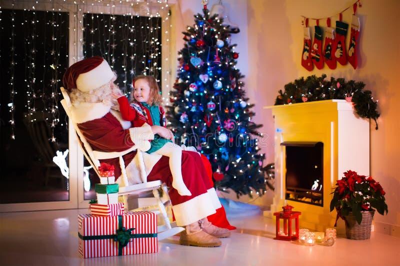 Jonge geitjes en de Kerstman die Kerstmis de openen stellen voor stock afbeelding