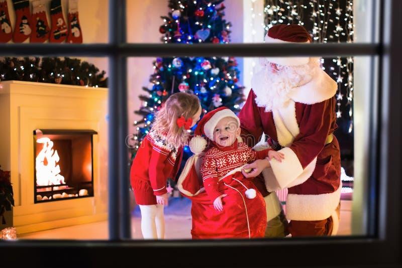 Jonge geitjes en de Kerstman die Kerstmis de openen stellen voor stock fotografie