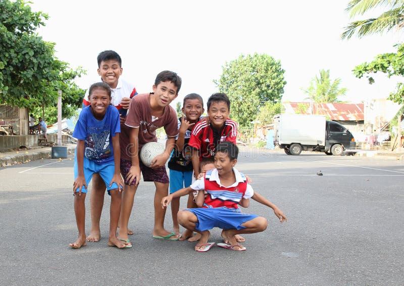 Jonge geitjes en tienerjaren die op straat in Manado stellen stock foto's