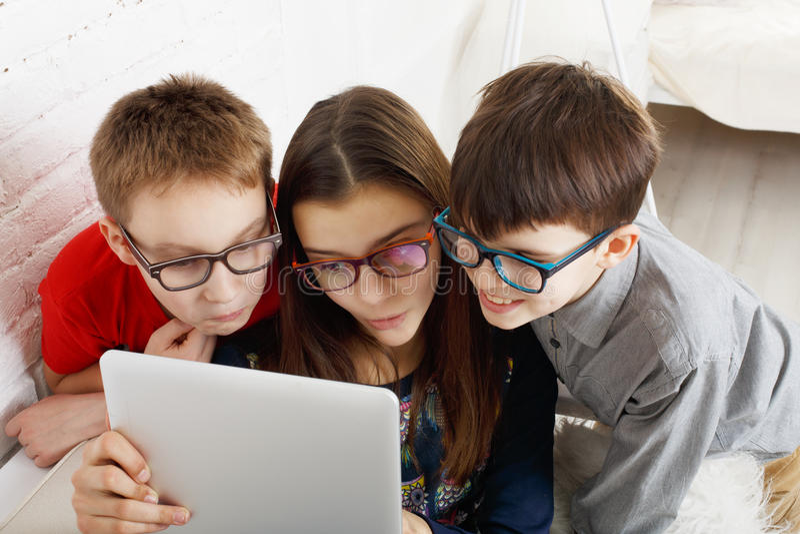 Jonge geitjes in glazen met tablet, computerverslaving stock afbeelding
