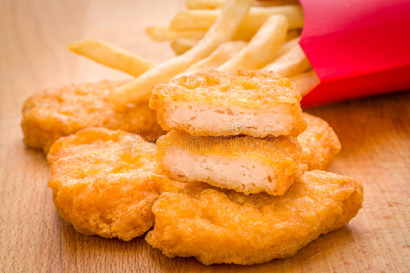 Jonge geitjes, goudklompjes en Frietenmaaltijd o van de kind de gouden bruine kip stock foto