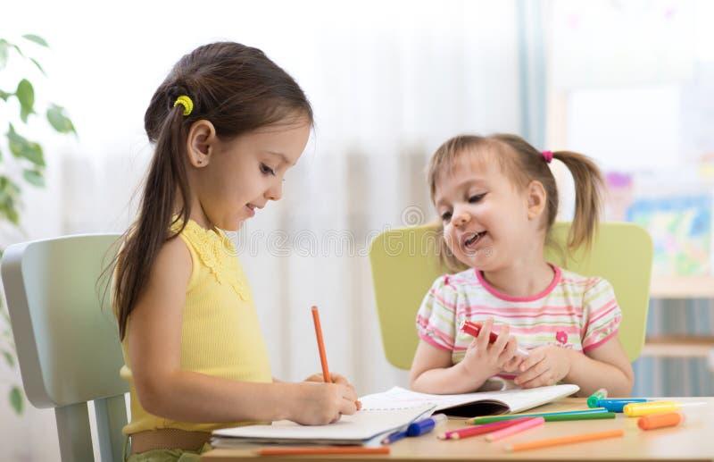 Jonge geitjes het trekken binnen kindergaten Kinderen die in kinderdagverblijf schilderen Kleuter met pen thuis Creatieve peuters stock afbeeldingen