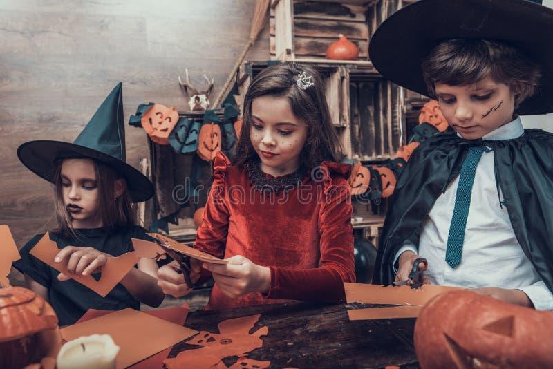 Jonge geitjes in Kostuums die Halloween-Decoratie maken stock foto's