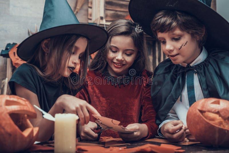 Jonge geitjes in Kostuums die Halloween-Decoratie maken stock fotografie