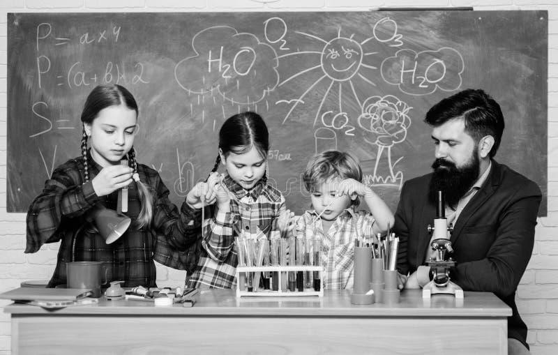 jonge geitjes in laboratoriumlaag het leren chemie in schoollaboratorium Chemielaboratorium gelukkige kinderenleraar Terug naar S royalty-vrije stock afbeeldingen