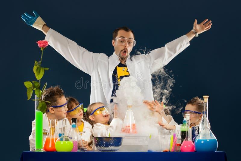 Jonge geitjes met gekke professor die wetenschapsexperimenten in het laboratorium doen royalty-vrije stock afbeeldingen