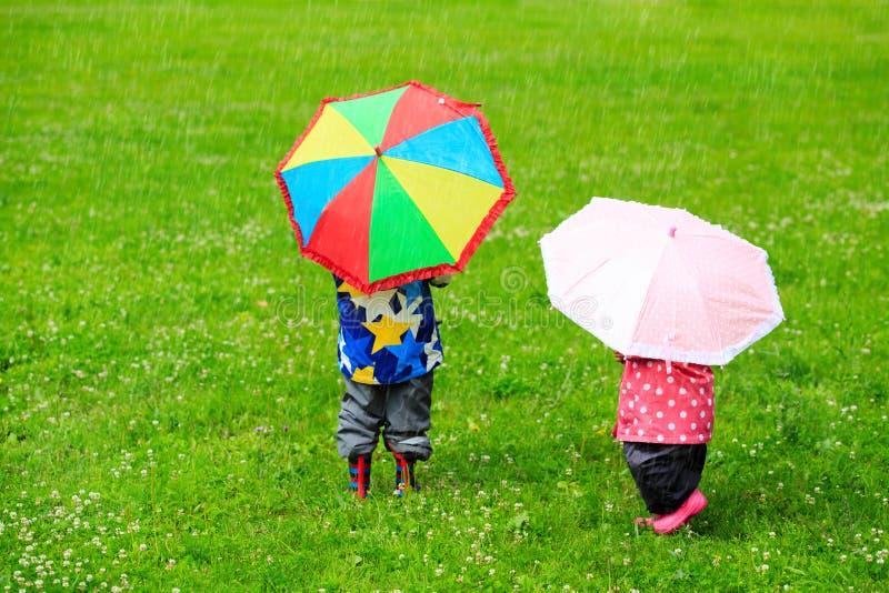 Jonge geitjes met kleurrijke paraplu's op regenachtige dag royalty-vrije stock foto's