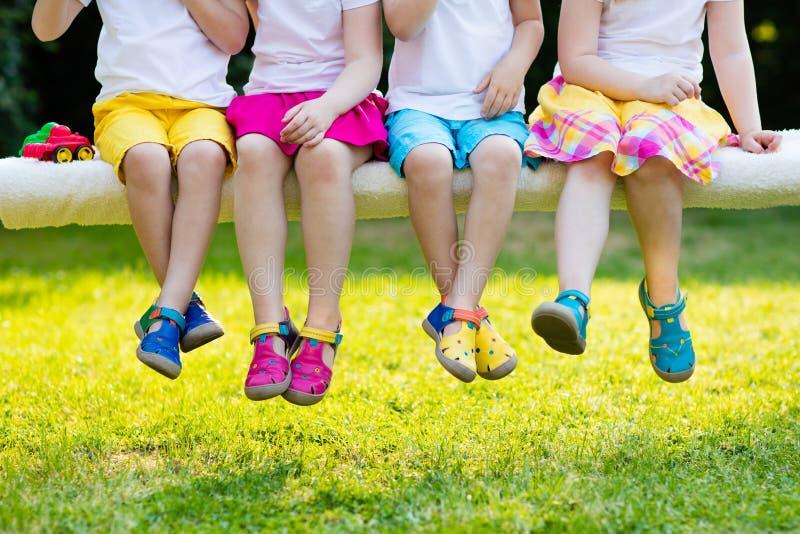 Jonge geitjes met kleurrijke schoenen Kinderschoeisel stock foto