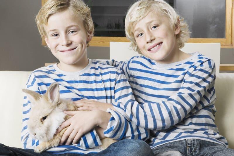 Jonge geitjes met Konijn thuis stock foto