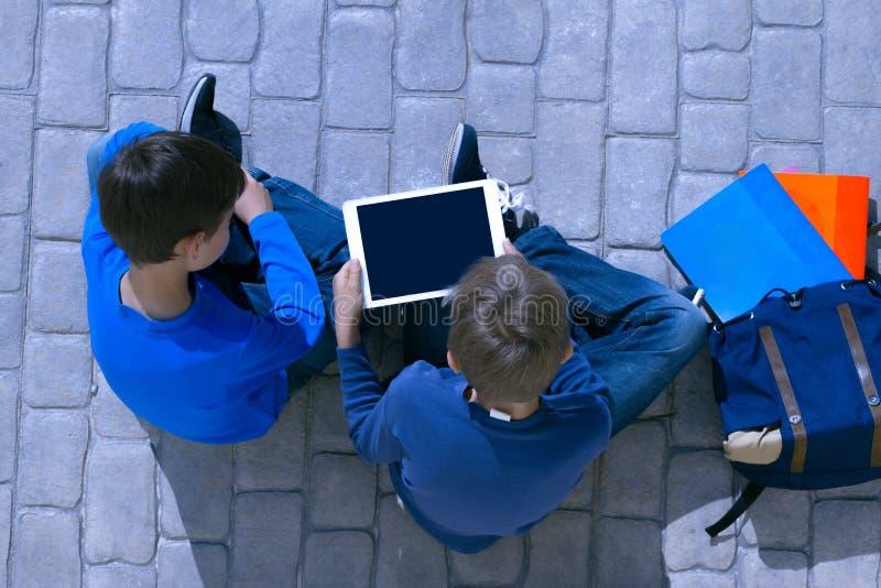 Jonge geitjes met van de tabletcomputer en rugzak zitting in openlucht stock foto's