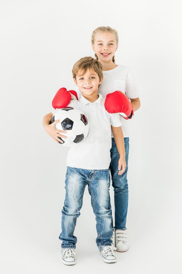Jonge geitjes met voetbalbal en bokshandschoenen stock foto