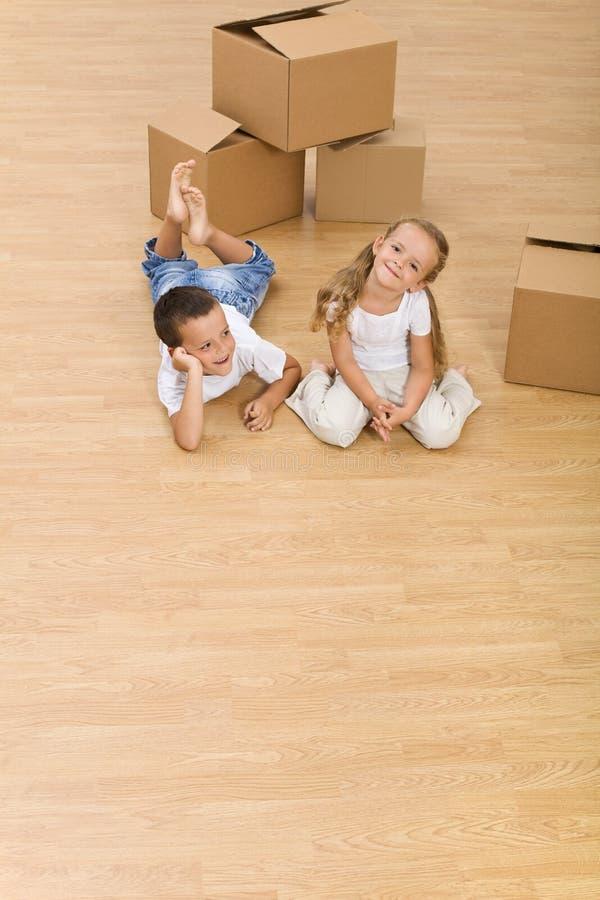 Jonge geitjes op de vloer in hun nieuw huis stock afbeelding