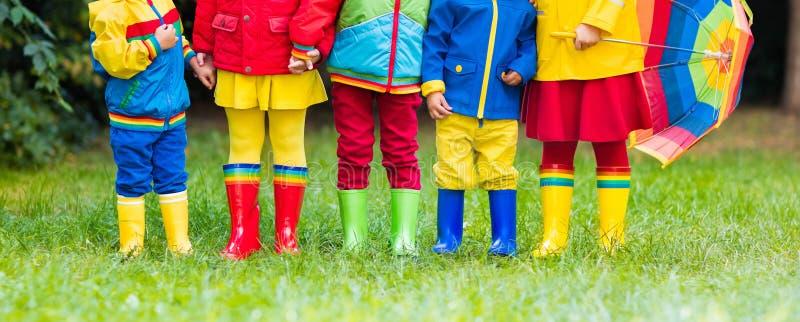 Jonge geitjes in regenlaarzen Rubberlaarzen voor kinderen royalty-vrije stock afbeeldingen