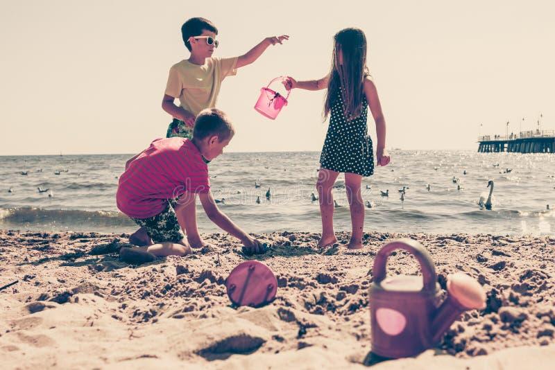 Jonge geitjes spelen openlucht op strand stock fotografie