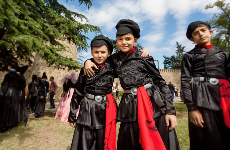 Jonge geitjes in traditionele Georgische kostuums die pret samen tijdens van stadsfestival hebben stock afbeelding