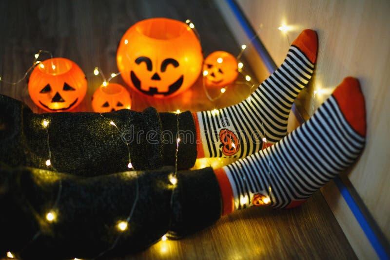 Jonge geitjesbenen in modieuze warme heldere kleurrijke gestreepte grappige sokken in slingerlichten op vloer met pompoenen in ru stock foto