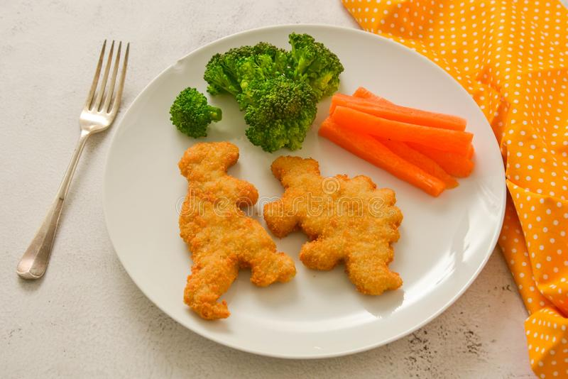 Jonge geitjesfood Goudklompjes met groenten Dinosaurus gevormde kip, vissen of van Turkije goudklompjes, klaar te eten royalty-vrije stock afbeeldingen