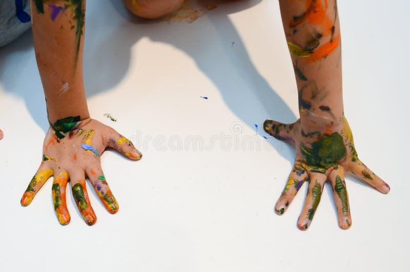 Jonge geitjeshanden met kleurrijke verf stock afbeelding
