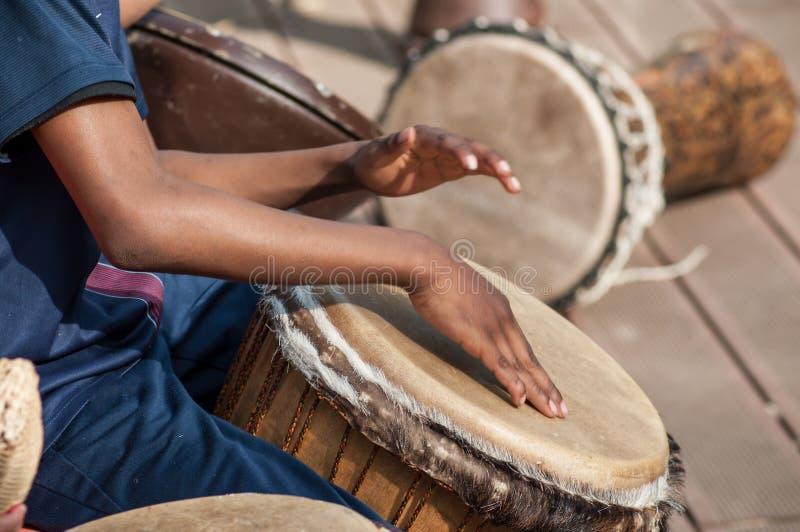 Jonge geitjeshanden op Afrikaanse trommels in openlucht stock foto's