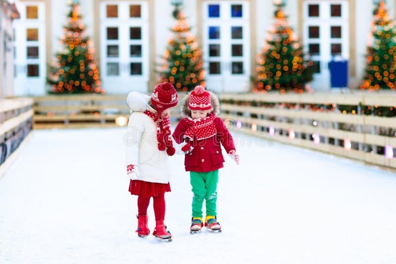 Jonge geitjesijs die in de winter schaatsen Schaatsen voor kind stock foto's