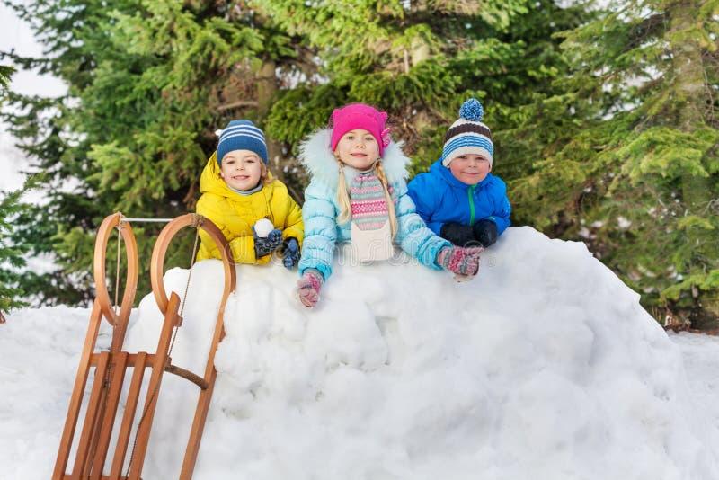 Jonge geitjesjongens en meisje achter sneeuwmuur met sneeuwballen stock afbeelding
