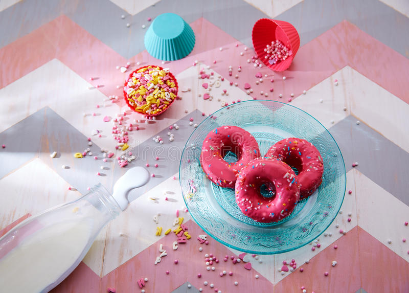 Jonge geitjespartij met melk roze donas en cupcake topings stock foto