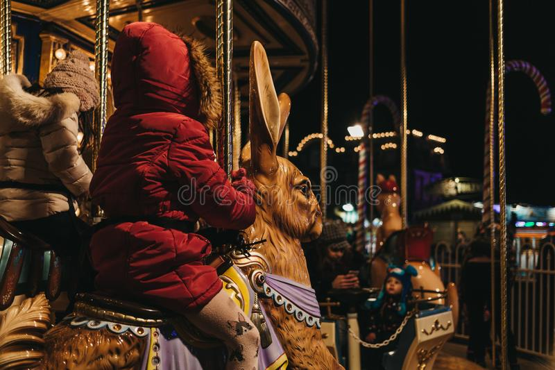 Jonge geitjesrit vrolijk-gaan-rond bij Kerstmismarkt van het de Wintersprookjesland in Londen, het UK royalty-vrije stock afbeelding